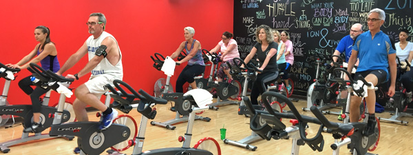 Community members participating in spinning exercise class
