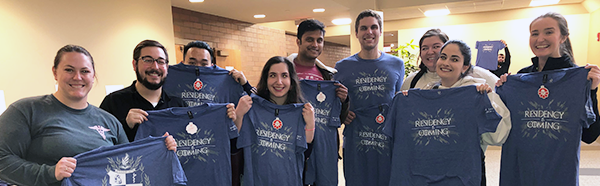 Medicine students holding their Match Day T-shirts