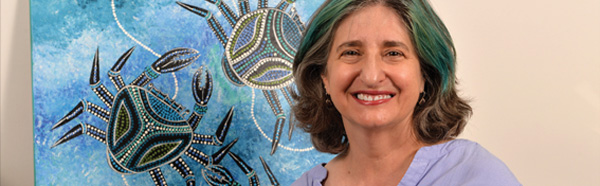 Rebecca German, Ph.D., in front of a painting