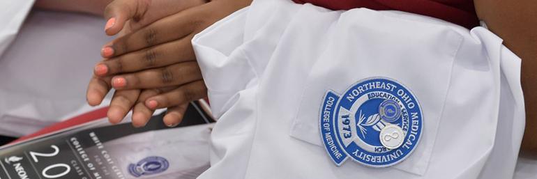 Student holding White Coat