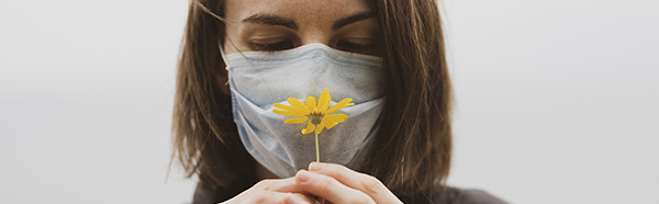 woman smelling flower while wearing a face covering