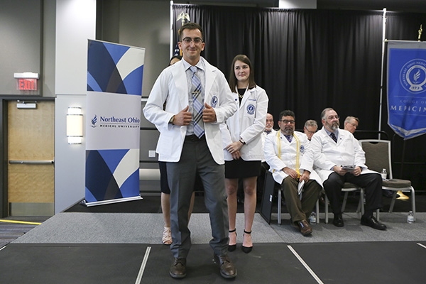 College of Medicine student putting on his white coat
