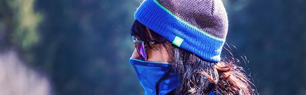 Woman wearing beanie, sunglasses and neck gaiter.